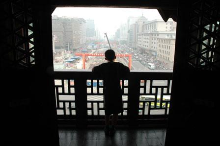 En dreng kigger ud fra Xians klokketårn