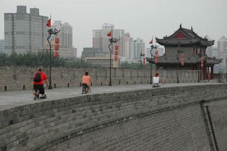 Tre glade cyklister på Xians bymur.